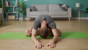 Den unga mannen g?r yoga p? vardagsrum i morgonen lager videofilmer