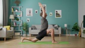 Den unga mannen g?r yoga p? vardagsrum i morgonen stock video