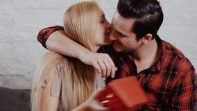 Den unga mannen ger en gåva till en flicka på soffan