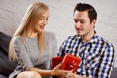 Den unga mannen ger en gåva till en flicka på soffan royaltyfri bild