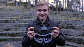Den unga mannen ger en virtuell verklighethörlurar med mikrofon i parkera Den unga mannen ger en virtuell verklighethörlurar med  Royaltyfri Bild