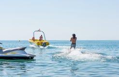 Den unga mannen glider på vattenskidåkning på vågorna på havet, havet Sund livsstil Positiva mänskliga sinnesrörelser, känslor royaltyfria foton