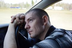 Den unga mannen grubblade i bilen royaltyfria foton
