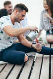 Den unga mannen häller te in i koppen på picknick arkivfoto