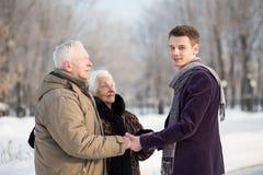 Den unga mannen hälsar ett äldre par i parkera Arkivbilder