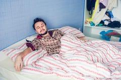 Den unga mannen hade precis vaknat upp i säng en Arkivbild