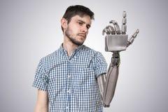 Den unga mannen har den robotic handen som ett utbyte för hans hand 3D framförde illustrationen av handen Arkivfoto
