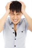 Den unga mannen har en huvudvärk och känner sig mycket smärtsam royaltyfri foto