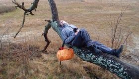 Den unga mannen har en vila som ligger på ett träd Fotografering för Bildbyråer
