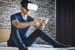 Den unga mannen har gyckel på sovrum i virtuell verklighethörlurar med mikrofon eller G 3d Royaltyfria Bilder