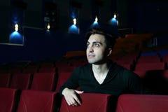 Den unga mannen håller ögonen på film och ler i filmbiograf. Royaltyfria Bilder