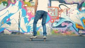 Den unga mannen hoppar på hans skateboard och starter som rider längs grafittiväggen lager videofilmer