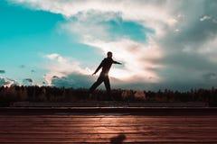 Den unga mannen hoppar på taket i solnedgång från sida royaltyfri foto