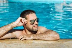 Den unga mannen, i att vila för solglasögon, kopplade av på kanten av simbassängen Royaltyfri Foto