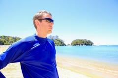 Den unga mannen i blå skjorta som tycker om den härliga apelsinen, sätter på land Royaltyfri Foto