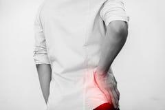 Den unga mannen i den tillfälliga kontorsskjortan som har höften, smärtar Arkivfoto