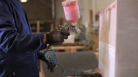 Den unga mannen i en möblemangfabrik applicerar ett lim på ett trästycke av soffan stock video