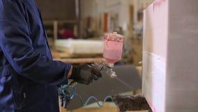Den unga mannen i en m?blemangfabrik applicerar ett lim p? ett tr?stycke av soffan arkivfilmer