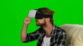 Den unga mannen i en VR-maskering något fångar händer grön skärm stock video
