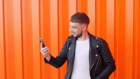 Den unga mannen i ett svart omslag med en telefon i hans händer fångar ett mobilt nätverk, en glad grabb grundar ett mobilt nätve stock video