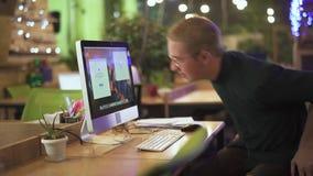 Den unga mannen i exponeringsglas sitter på hans arbetsplats framme av den moderna datoren i stort kontor Bakgrund ?r suddig Begr arkivfilmer