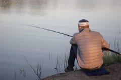 Den unga mannen i grå färgomslag är sitta och fiska på en sjökust i mitt--sommar afton royaltyfria foton