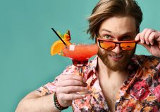 Den unga mannen i hatt och solglasögon som dricker den röda margaritacoctailen, dricker den lyckliga seende kameran för fruktsaft royaltyfria bilder