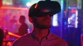 Den unga mannen i huvud-monterad skärm ser omkring, virtuell verklighet, hmd 360 arkivfilmer