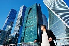 Den unga mannen i klassiskt klädanseende på en bakgrund av skyskrapor Begreppet av framgång och utveckling arkivbilder