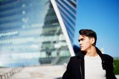 Den unga mannen i klassiskt klädanseende på en bakgrund av skyskrapor Begreppet av framgång och utveckling royaltyfri fotografi