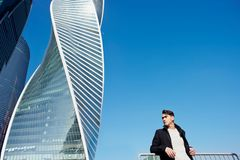 Den unga mannen i klassiskt klädanseende på en bakgrund av skyskrapor Begreppet av framgång och utveckling royaltyfria bilder