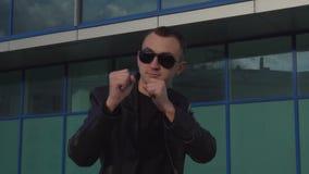 Den unga mannen i läderomslag och solglasögon som står i strid, poserar utomhus- arkivfilmer