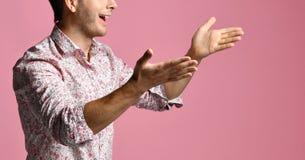 Den unga mannen i skjorta har en dialog som gestikulerar med öppna händer, gömma i handflatan att le på rosa färger royaltyfri bild