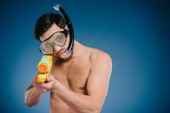 den unga mannen i snorkel och dykning maskerar det hållande vattenvapnet Arkivbild
