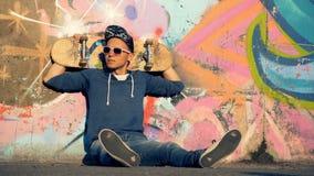 Den unga mannen i streetwear sitter på jordningen med en skateboard bak hans huvud lager videofilmer