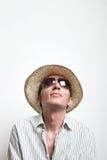 Den unga mannen i sugrörhatt och solglasögon ser upp Arkivbild