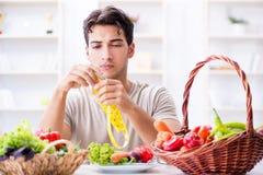 Den unga mannen i sunt äta och banta begrepp royaltyfri bild
