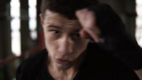 Den unga mannen i svart T-skjorta fullgör slag i svart boxning förbinder och se allvarligt på kameran i idrottshallen close upp arkivfilmer
