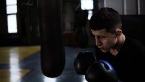 Den unga mannen i svart T-skjorta fullgör slagen som övar med den stora tunga boxas påsen på idrottshallen Starka stansmaskiner s arkivfilmer