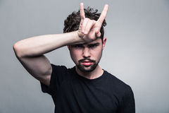 Den unga mannen i svart T-tröja med den trendiga frisyren visar horn arkivbild