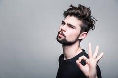 Den unga mannen i svarta T-tröjashower gör en gest ok royaltyfria bilder