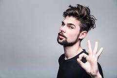 Den unga mannen i svarta T-tröjashower gör en gest ok arkivbild