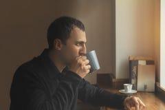 Den unga mannen i tillfällig kläder dricker kaffe, medan sitta i en caf Royaltyfri Bild