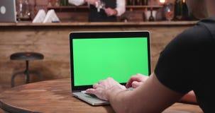 Den unga mannen i tillfälliga clothertyper fastar på en bärbar dator med den gröna skärmen stock video
