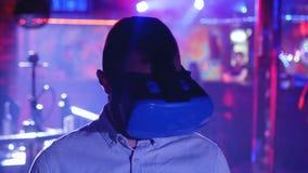 Den unga mannen i vrhörlurar med mikrofon ser omkring, virtuell verklighet, huvud-monterad skärm stock video
