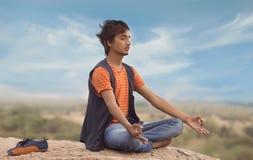Den unga mannen i yoga poserar arkivfoto