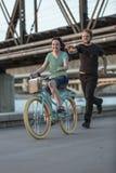 Den unga mannen jagar flickan på cykeln Arkivbild