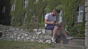Den unga mannen klarar av data från smartphonen till bärbara datorn arkivfilmer