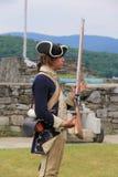Den unga mannen klädde som soldaten som visar, hur en musköt laddas och avfyras mot fienden, fortet Ticonderoga, New York, 2014 Arkivfoton