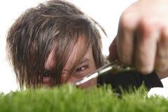 Den unga mannen klipper engelsk gräsmatta Royaltyfri Fotografi